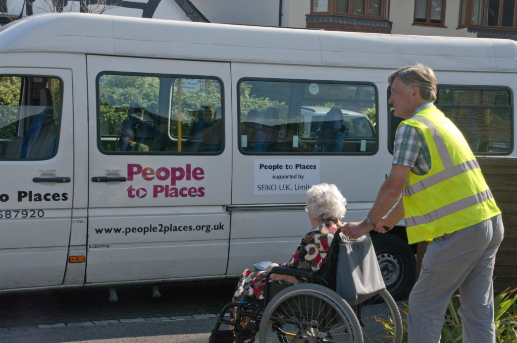 community Transport driver pushing a passenger in a wheelchair
